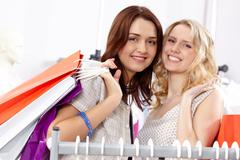 Stock Photo of close-up of two happy women carrying bags and looking at camera with smiles