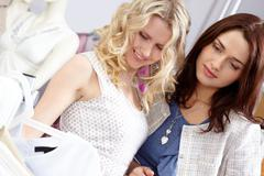 portrait of young girls in the department store chosing new clothes - stock photo