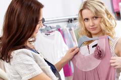 image of pretty girl trying on tanktop with helpful assistant near by in the dep - stock photo