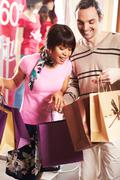 portrait of pretty female showing bags to happy man after shopping - stock photo