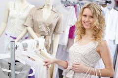 portrait of pretty blonde choosing new tanktop and looking at camera in clothing - stock photo