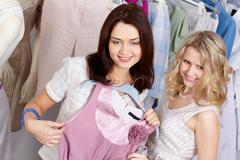 image of pretty friends chosing new fashionable clothes in the department store - stock photo