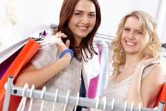 close-up of two happy women carrying bags and looking at camera with smiles - stock photo