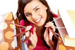 Portrait of happy girl with colorful paper bags looking at camera with smile Stock Photos