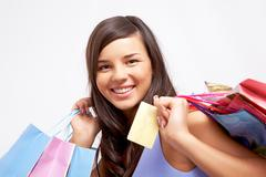 portrait of happy girl with colorful paper bags and plastic card looking at came - stock photo