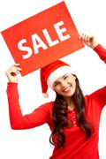 happy girl in santa cap holds card with symbol of sale - stock photo