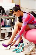 Image of lady trying on several pairs of new shoes in the mall Stock Photos