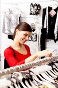 portrait of pretty woman choosing new clothes in the mall - stock photo