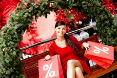 Happy girl holds red paperbags with symbol of sale in market Stock Photos