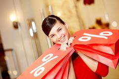 Happy girl holds red paperbags with symbol of sale and looking at camera Stock Photos