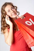 Stock Photo of portrait of a girl holding paper bags with discount symbol, calling on the cellp