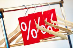 image of several wooden hangers with red discount tags - stock photo