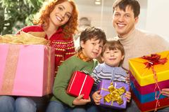 Portrait of family holding giftboxes in the shop Stock Photos