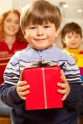 Portrait of happy child holding red gift box Stock Photos