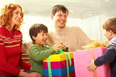 Image of parents with son looking at boy with big pink gift box Stock Photos