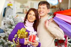 image of attractive couple looking aside and smiling in trade center - stock photo