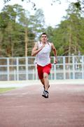 Stock Photo of image of energetic sportsman running down stadium track