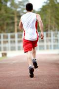 Rear view of energetic sportsman running down stadium track Stock Photos