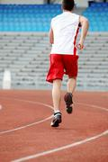 Stock Photo of back of guy in sportswear running down stadium track