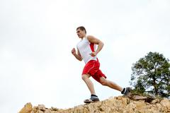 image of healthy athlete running down cliff - stock photo