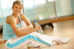 Healthy teenage girl sitting on the floor with bottle of water in hand and looki Stock Photos
