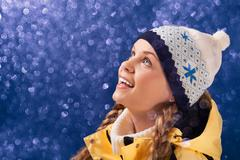 portrait of amazed girl looking at sparkling snowfall - stock photo