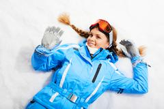Portrait of woman in sporty clothes resting on snow Stock Photos