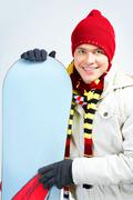 portrait of healthy man with snowboard looking at camera and smiling - stock photo