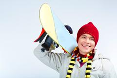 photo of skillful teenager with snowboard on his shoulder over blue background - stock photo