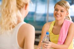 Generous girl giving bottle of water to the friend in front of her Stock Photos