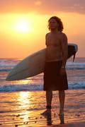 Portrait of young man standing on seashore with windsurf board at sunset Stock Photos