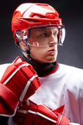 portrait of sportsman in hockey uniform over black background - stock photo