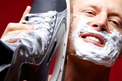 Portrait of young man with foam on face shaving with skate razor Stock Photos