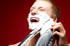 Young man with foam on face shaving with skate razor Stock Photos