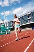 photo of sporty female running on stadium - stock photo