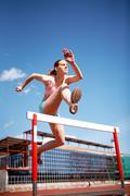 Image of young female jumping over barrier Stock Photos