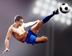 professional footballer kicking soccer ball - stock photo