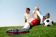 Photo of soccer player sitting on green grass-field and resting Stock Photos