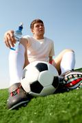 photo of pensive soccer player seated on green grass-field against blue sky - stock photo