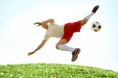 image of soccer player during flying kick - stock photo