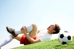 Image of soccer player lying down and shouting in pain Stock Photos