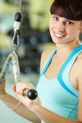 Photo of happy girl pumping muscles on special equipment Stock Photos