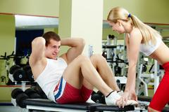Portrait of sporty female helping handsome guy do physical exercise in gym Stock Photos