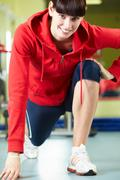 photo of sporty brunette in sportswear doing exercise on the floor of gym - stock photo