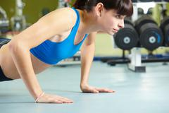 photo of young girl doing difficult exercise for arm biceps on the floor - stock photo