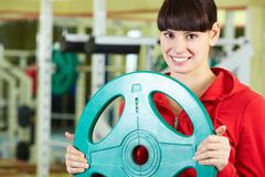 Photo of fit brunette with bars for weight in sport gym Stock Photos