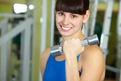 portrait of young female with dumbbell doing exercise - stock photo