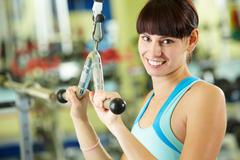 photo of active girl pumping muscles on special equipment - stock photo