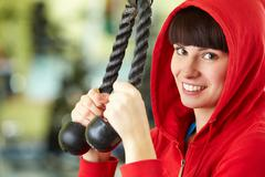 photo of happy girl doing physical exercise on special equipment - stock photo