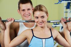Portrait of sporty woman holding dumbbell and her trainer supporting Stock Photos